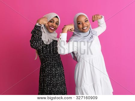two african girls  wearing traditional islamic clothes on plastic pink background  showing  strenght and power gender equality