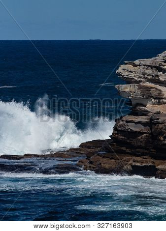 Oceanside Rocky Sandstone Cliff With Blue Sea Water Waves Creating Whitewash Against Coastline And C