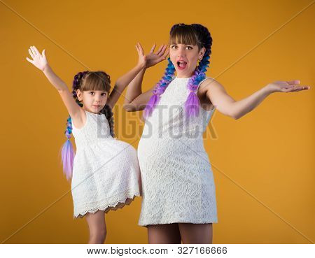 Funny Mom And Daughter Posing In The Studio With A Pregnant Belly And Mimicking A Pregnancy With A B