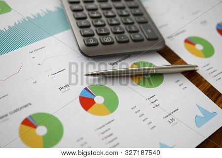 Focus On Biz Document With Charts, Graphs, Pen And Calculator. Important Paper With Annual Report Of