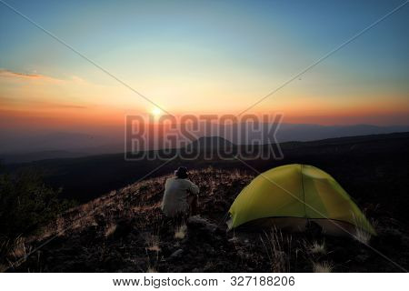 hiker with hat overlooking sunset from high altitude wild camp in Etna Park at twilight, Sicily