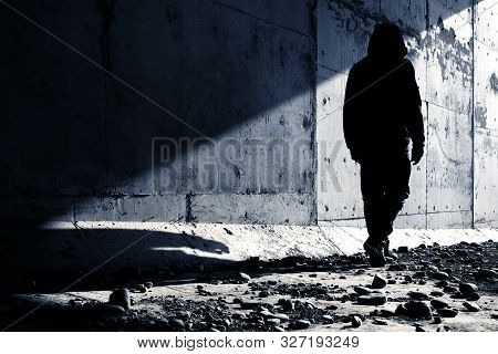 A Man Going Out Of An Abandoned Tunnel Leaving A Strong Shadow Behind. Man Going To Light.