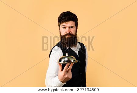 Waiter Holds Metal Tray With Lid. Professional Waiter In Uniform. Serious Butler With Serving Tray.