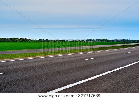 Asphalt Road Or Highway Closeup Against The Background Of Rural Landscape With Green Sown Field And