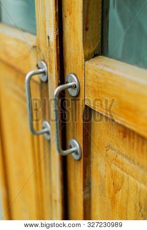 Metal Handle On A Brown Wooden Door. Black Wicker Handle On The Old Door. Metal Handle On A Brown Wo
