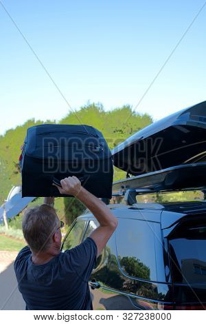 Man Loading Suitcase Into Roof Box On Top Of Car
