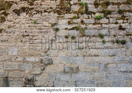 Fragment Of The Fortress Wall Of The Same Stone Blocks. There Are Damage From Time And Moss On The W
