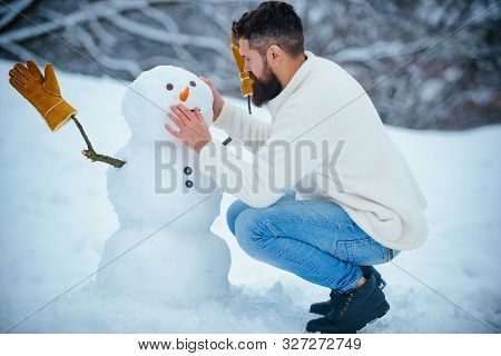 Snowman And Funny Bearded Man In The Snow. Man Playing With Snowman - Isolated On Snow Background. J