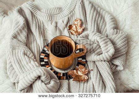 Still Life With Gold Leaves And A Yellow Large Cup Of Tea Wrapped Snugly In A Sweater . The Concept