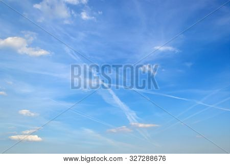 Jet Trails In The Sky With White Translucent Cirrus Clouds. Many Airplane Contrails In A Blue Sky On