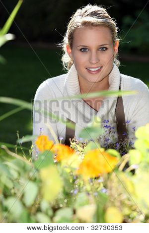 young woman standing behind flowers
