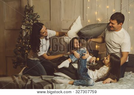 Christmas Time With Family. Happy Young Cheerful Parents Fighting Pillows With Two Daughters. Light