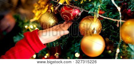 Side view close up of a hand of a young Caucasian girl decorating the Christmas tree in the sitting room at Christmas time