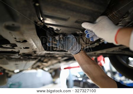 Focus On Hardworking Male Hands Examining Modern High-tech Automobile Underneath Pipes In White Glov
