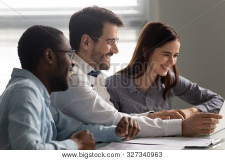 Overjoyed Multiracial Teammates Watching Funny Video Together.
