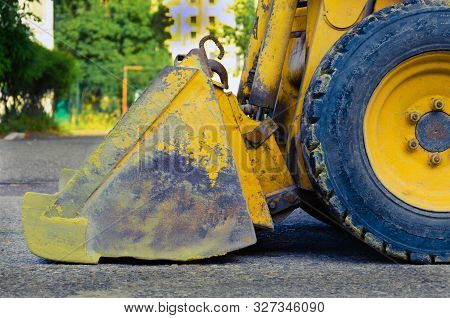 Bucket And Wheels Of Heavy Construction Equipment. Side View. Yellow Metal Bucket With Scratches. Di