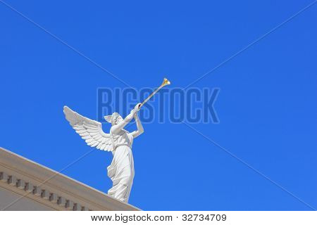 A white statue of a winged troubadour against the blue sky. The statue is installed on the roof eaves