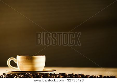brown coffee cup on brown background with coffee beans