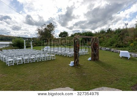 Place For Wedding Ceremony At The Lakeshore. Wedding Arch Decorated With Flowers And White Chairs On