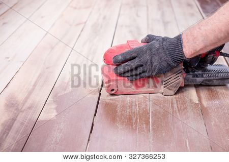 Wood Floor Polishing Maintenance Work By Grinding Machine. Copy Space. Repair In The Apartment.speci
