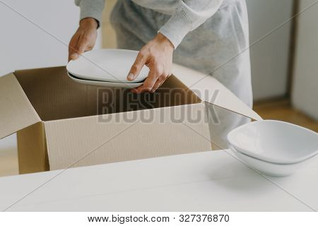 Cropped Image Of Unknown Faceless Busy Man Unpacks Boxes With Dishes, Holds White Plates, Moves In N