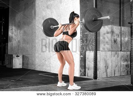 Side View Of A Woman In The Gym. Hard Training. Squats. Side-back View.