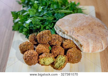 Falafel Balls, Pita And Green Fresh Parsley On Wood Rustic Background. Falafel Is A Traditional Midd