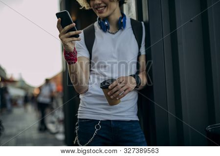 Cheerful Guy With Smartphone Drinking Coffee Outdoors Stock Photo
