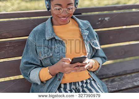 Jolly Girl Enjoying Music On Gadgets Outdoors Stock Photo