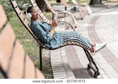 Happy Woman With Earphones Reading In Park Stock Photo