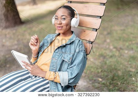Happy Girl With Notepad Having Rest In Park Stock Photo