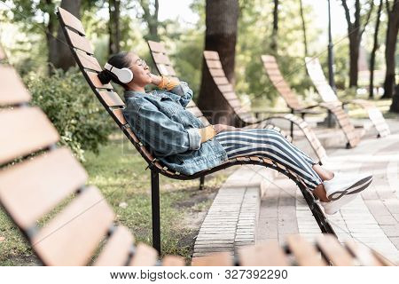 Young Woman Resting With Headphones In Park Stock Photo
