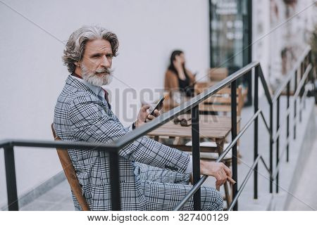 Serious Man With Smartphone And Cigar Sitting Alone Stock Photo