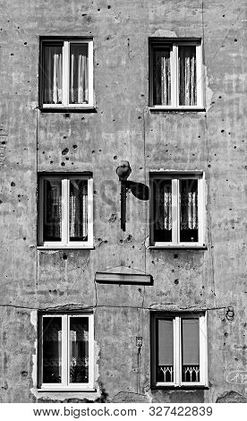 Monochrome image of old tenement in capital of Poland Warsaw in Praga district with second world war marks of shots on its parget poster