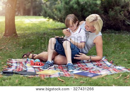 Concentrated Youngster And His Mother Scrolling Web Via Tablet During Park Lawn Rest