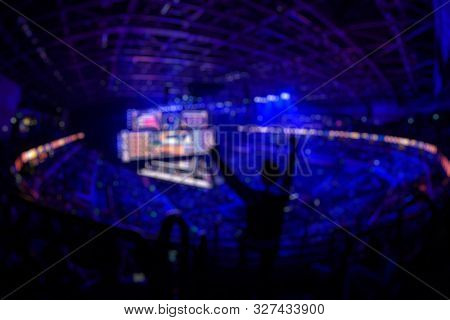 Blurred Background Of An Esports Event - Fan On A Tribune At Tournaments Arena With Hands Raised.