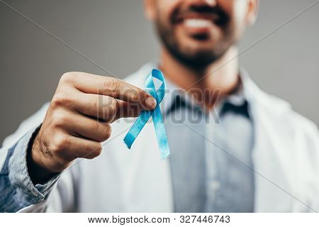 Prostate Cancer Awareness. Doctor Man Holding Light Blue Ribbon For Supporting People Living And Ill