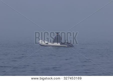 Fisherman In Inflatable Fishing Boat With Outboard Motor Moving In The Dense Fog.