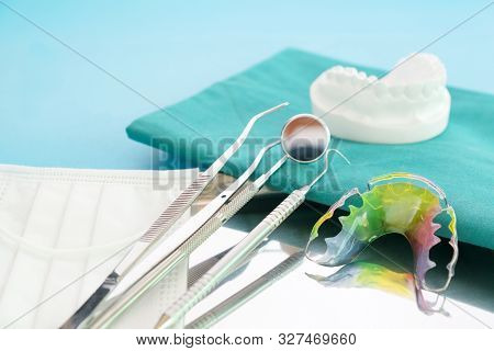 Dental Retainer Orthodontic Appliance And Dental Tools On The Blue Background.