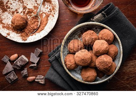 Homemade Dark Chocolate Truffles On Plate, Brown Wooden Background. Table Top View. Chocolate Candy
