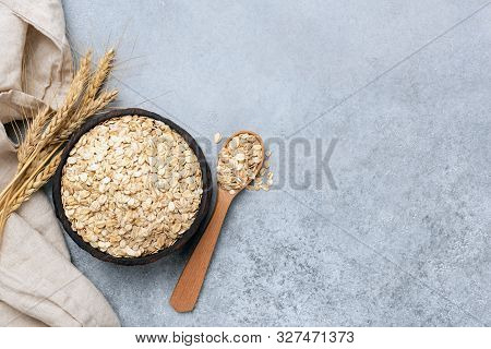 Bowl Of Rolled Oats Oat Flakes On Concrete Background With Copy Space. Clean Eating, Dieting, Weight