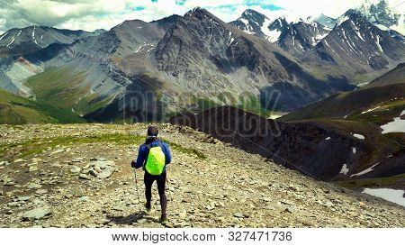 A Tourist With A Backpack Walks Along A Mountain Path, Background For Outdoor Travel.