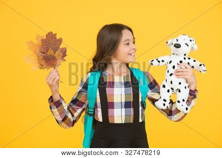 Nourish Child With Game. Small Child Hold Toy Doll And Autumn Leaves. Little Girl Play Game In Schoo