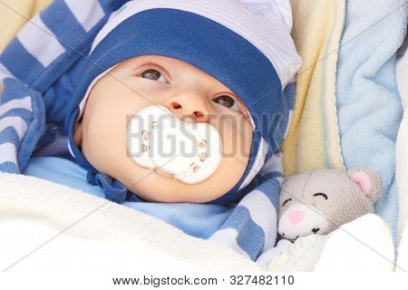 Sweet Little Newborn Baby With Pacifier In Babies Pram With Toy Teddy Bear
