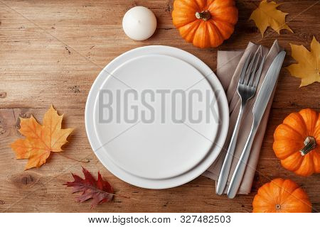 Autumn Thanksgiving Table Setting For Dinner With Plate, Knife, Fork Decorated Pumpkins And Maple Le