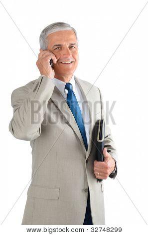 Middle aged zakenman spreken op zijn mobiele telefoon en de uitvoering van een binder. Man is glimlachend en op zoek