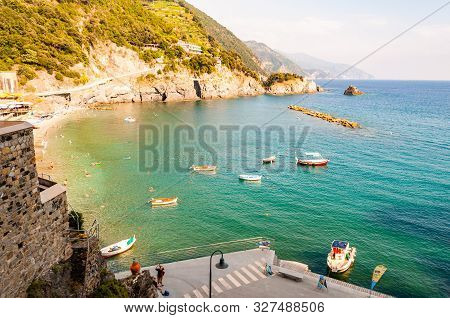 Monterosso Al Mare, Italy - September 02, 2019: Rocky Coastline With Floating Boats And The Beach Wi