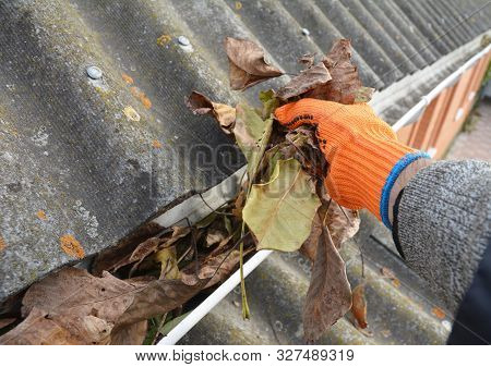 Roofer Hand Cleaning Rain Gutter From Leaves In Autumn. Roof Gutter Cleaning From Fallen Leaves. Hou