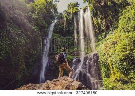 Man In Turquoise Dress At The Sekumpul Waterfalls In Jungles On Bali Island, Indonesia. Bali Travel