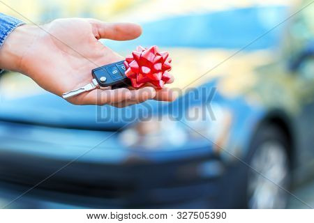 Closeup Male Hand Of New Black Car Is Holding Gift, Surprise, Keys With Red Bow. Lucky Driver Is Goi